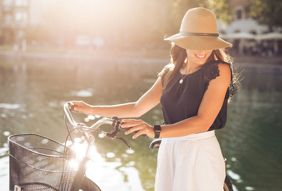Elegant woman with bike by the river on a sunny day