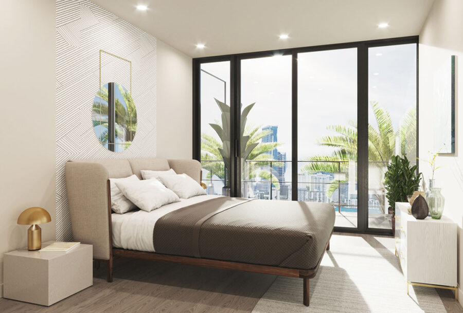 Bedroom with accent wall, large floor to ceiling sliding doors to balcony/patio, queen sized bed and additional furniture