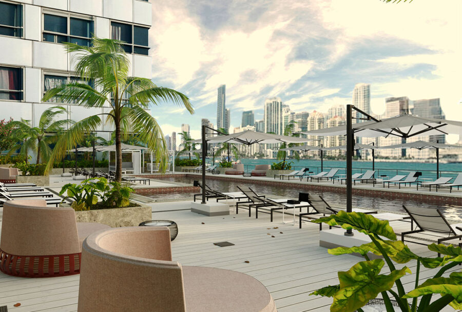 Outside deck with a variety of lounge seating, umbrellas, tropical landscaping and resort-style pool