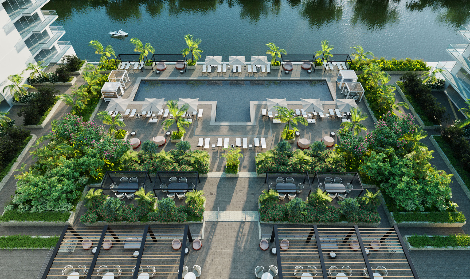 Aerial view of resort-style pool by the River Walk with lush landscaping, lounge seating, umbrellas, and covered seating