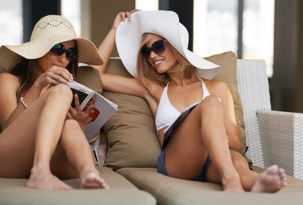 Two woman sunbathing by the pool with designer hat and magazines