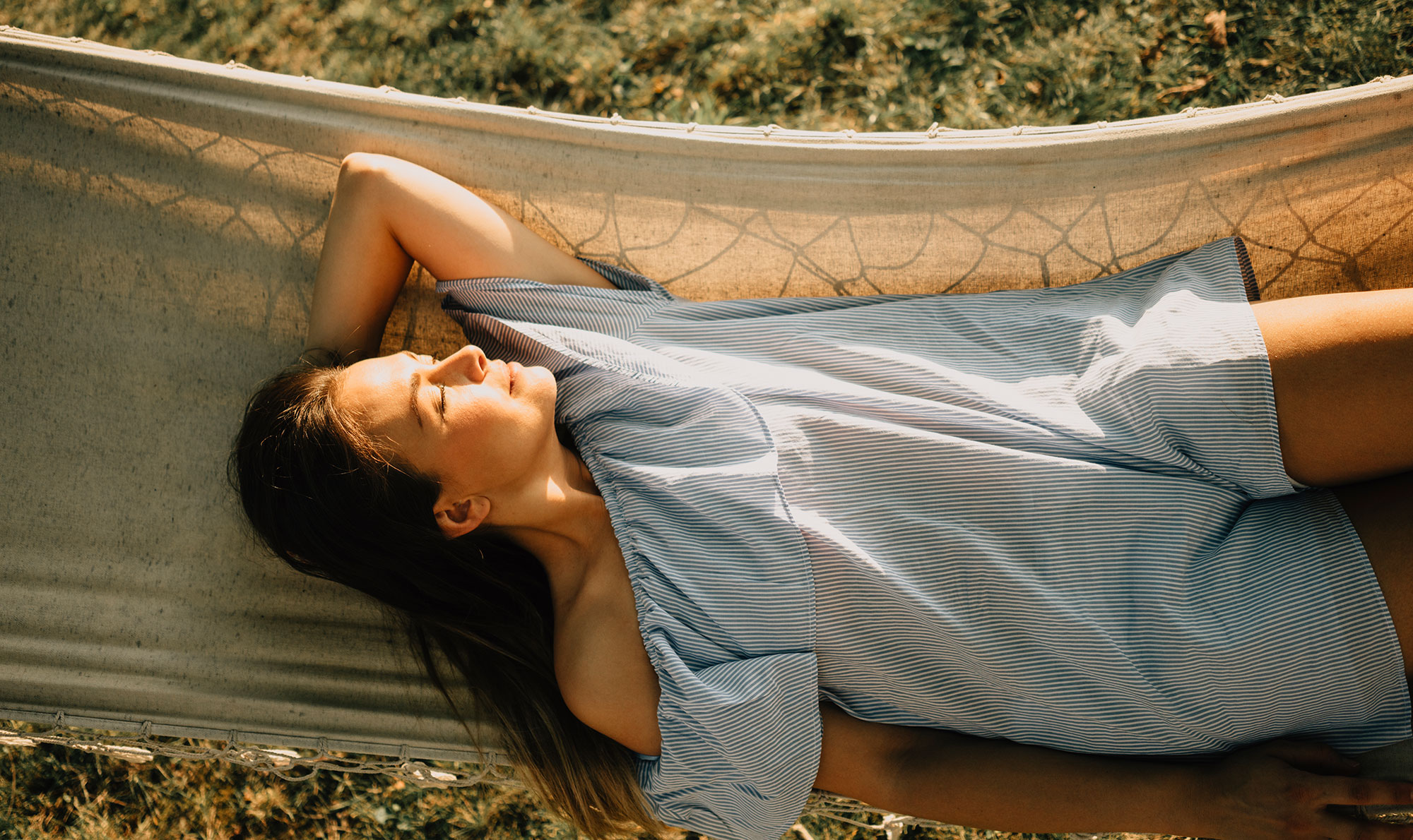Woman lying in hammock at sunset