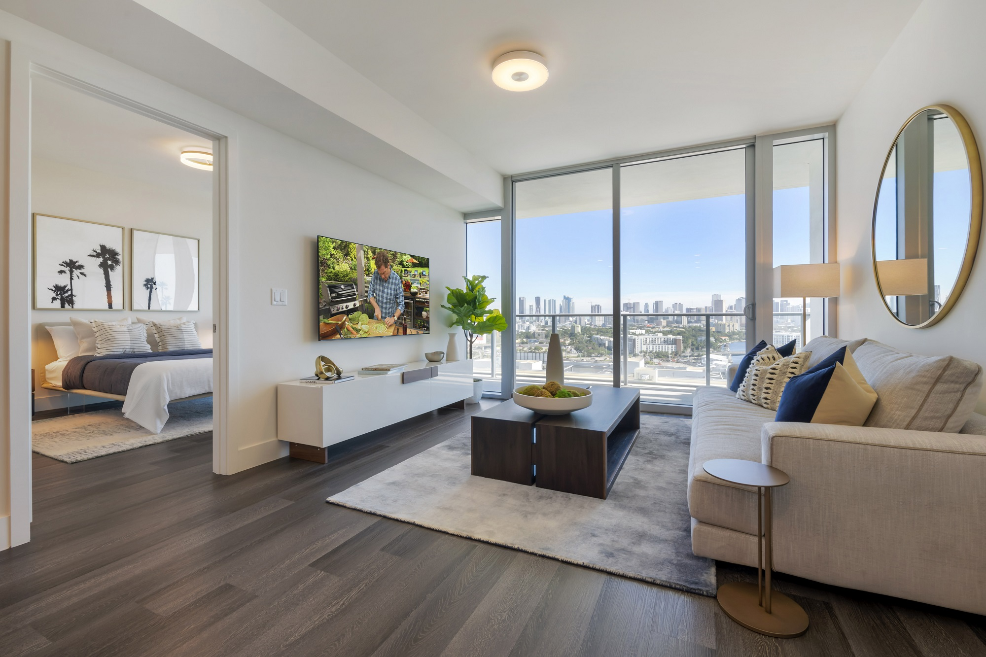 Living room with wood-style floors, floor to ceiling windows, door to balcony and accent wall