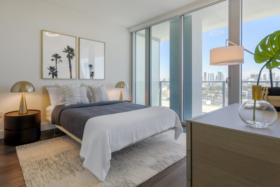 Bedroom with hardwood-style floors, floor to ceiling windows with patio access, and accent wall